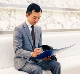 AGA専門クリニック 受付カウンター前のソファーで問診票に記入